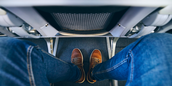 mans legs in an airplane seat with average pitch
