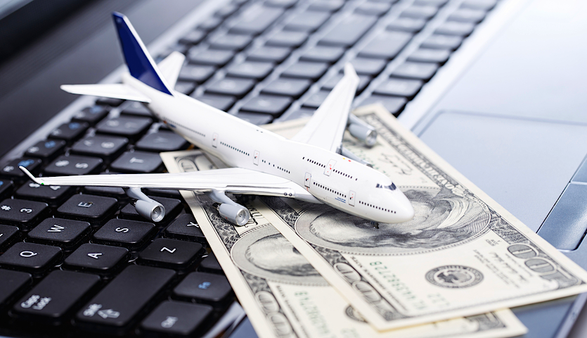 airplane with cash on a keyboard booking fees