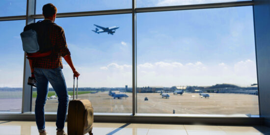 man with carry-on bags staring out window at terminal