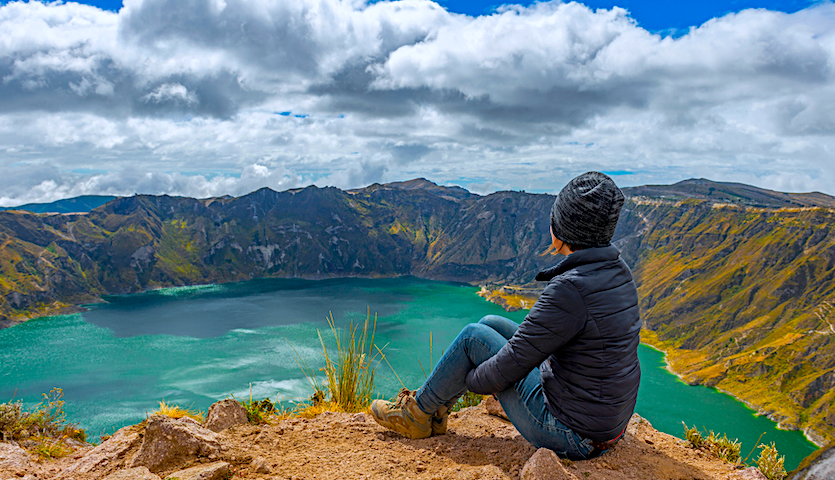 Woman sitting by a crater outside of Quito Ecuador