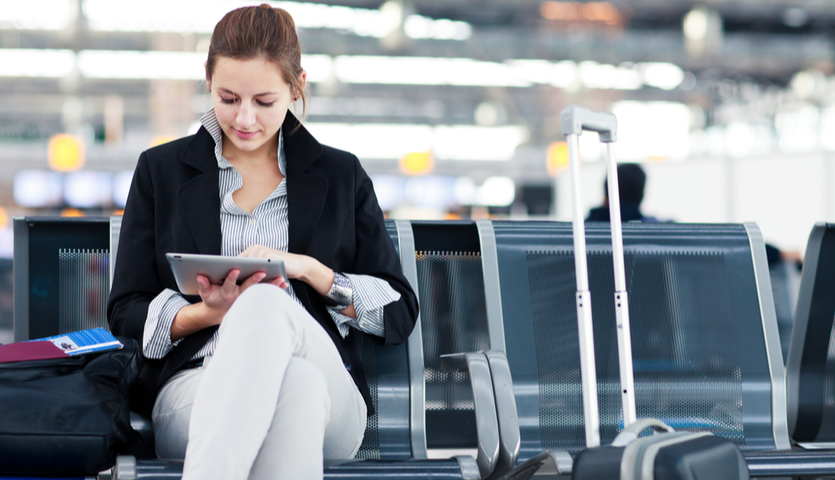 woman on tablet sitting at terminal in airport