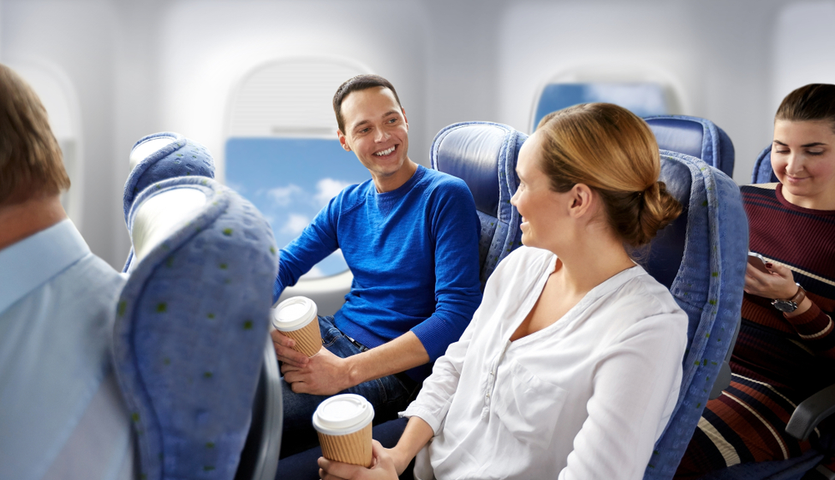 happy-couple-seated-on-plane-with-coffee