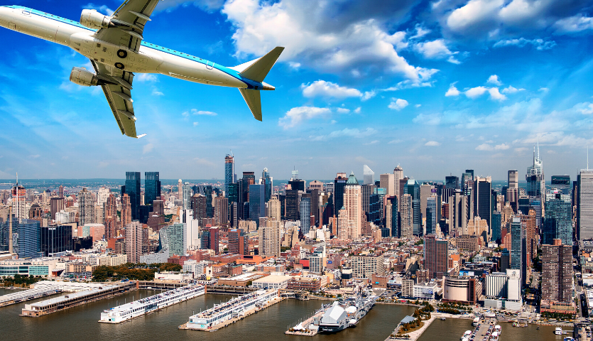 airplane flying above the new york city skyline